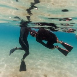 Two scuba divers underwater practicing apnea and surf survival skills