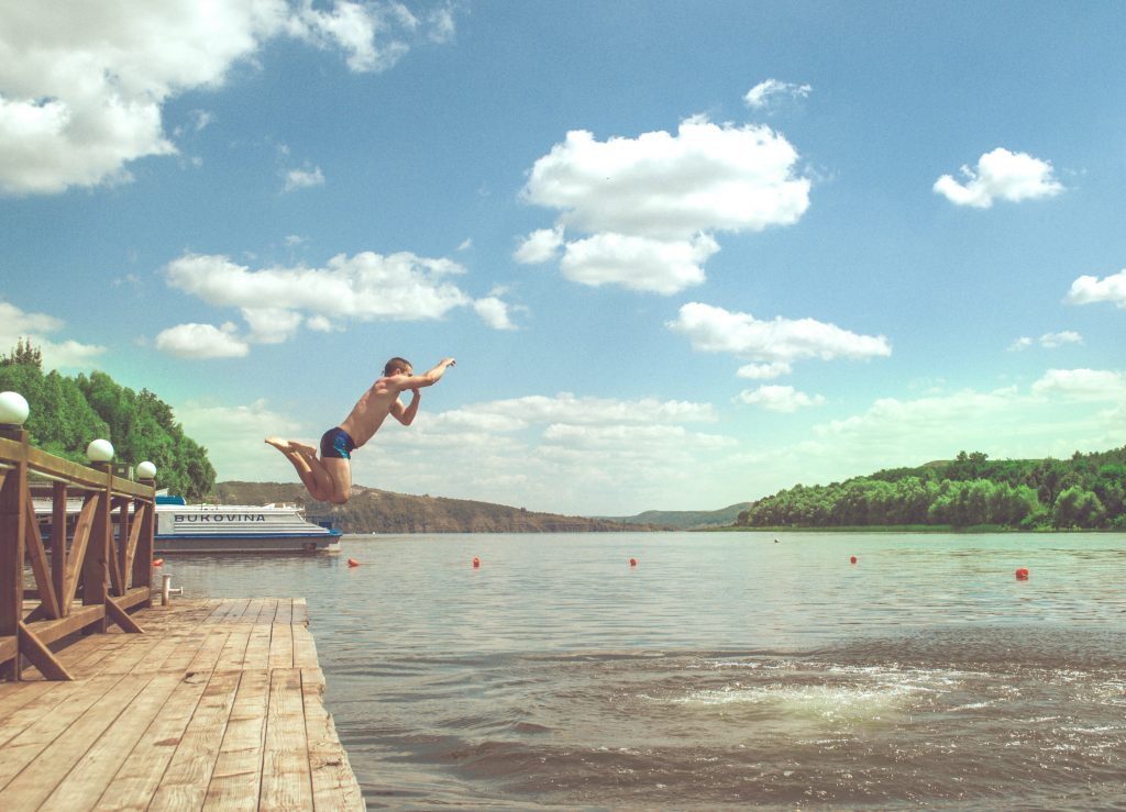 man jumping into water off dock with speedo to wear under a wetsuit
