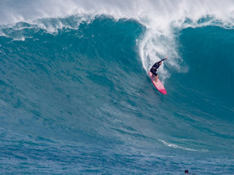 Surfer riding huge wave North Shore of Oahu with the help of apnea training