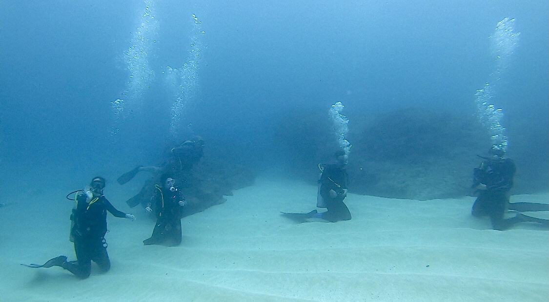 Newly trained PADI Rescue Divers await instruction underwater from the dive instructor.